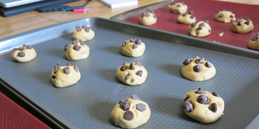 Biscuits aux pépites de chocolat prêts à cuire, disposés sur des plaques